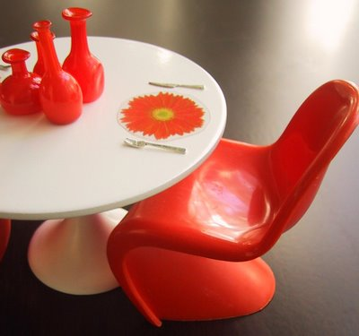 Modern dolls' house miniature Saarinen table with orange Panton chair, glass bottles and flower-shaped place mats.