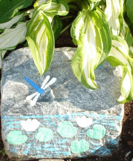 Dragonfly rock painting in the garden