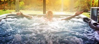 man waves from hottub