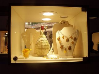 una vetrina della gioielleria con un fiasco di vino toscano