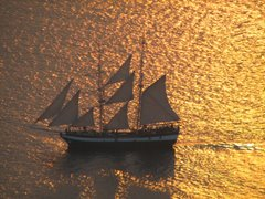 Sunset at Oia view three - sailboat on golden water...