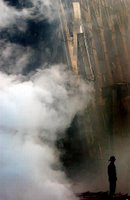 A solitary firefighter stands amidst the rubble and smoke in New York City, Sept. 14, 2001. Days after the Sept. 11 terrorist attack, fires still burn at the site of the World Trade Center. Photo by Photographer's Mate 2nd Class Jim Watson, USN