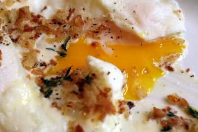 photograph picture of the broken yolk of cocotte-cooked egg with reduced cream and thyme breadcrumbs, comfort on a rainy stormy day