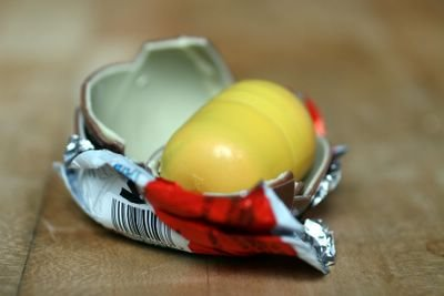 photograph picture how to unwrap and eat a kinder egg surprise. what is inside the egg?