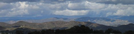 De bergtoppen door ons raam gezien met de eerste sneeuw van het jaar, hier verstopt onder een pak wolken met nieuwe sneeuw.