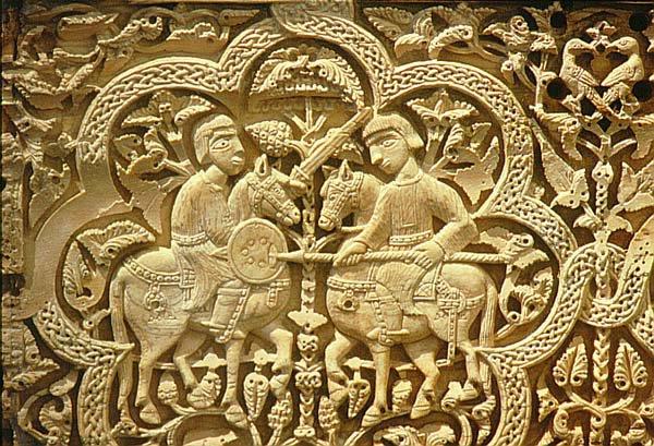 Arqueta hispano-árabe de marfil, llamada 'Arqueta de Leire'. (Taller de Medinat Az-Zahira, 395 Hégira / 1004-5 d.C.) 38 x 23,5 x 23 cm. La base de la tapa presenta una inscripción: 'En el nombre de Alá, bendición de Alá prosperidad, alegría, esperanza de obras buenas, retraso del momento supremo para el Hayb Saif al-Dawin Abd al-Malik ibn al-Mansur. Dios le asista, de lo que mandó hacer por orden suya bajo la dirección del Fata al-Kabir Zuhayr ibn Muhammad al-Amiri, su esclavo. Año cinco y noventa y trescientos'. En una de las inscripciones se puede leer que 'Fue hecha por Faray con sus discípulos'. Firmada por: 'Maestro Faray', 'Misgan', 'Rasid', 'Jaid' y 'Sa Abada'. - Es una caja rectangular con tapa en forma de pirámide truncada formada por 19 placas de marfil, talladas todas ellas excepto dos. La mayoría de la decoración se muestra en 21 medallones de ocho lóbulos mientras que el resto son motivos vegetales entre los que aparecen pájaros, animales y dos bustos. Los medallones de la parte frontal nos muestran escenas cortesanas. El panel posterior presenta escenas de lucha y de caza mientras que en los paneles laterales se representan animales. En la tapa aparecen escenas de caza y pavos reales. Durante muchos años esta arqueta fue utilizada como relicario en el monasterio de Leyre, pasando después a la iglesia de Santa María la Real de Sangüesa y después al tesoro de la catedral de Pamplona