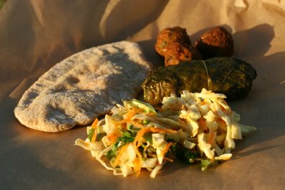 photograph picture of a vegan picnic of falafel, dolmades, homemade pitta and coleslaw with recipe links