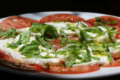 photograph picture of a simple heirloom tomato, fresh basil and mozzarella salad drizzled with olive oil and sesoned with New Maldon salt and freshly ground black pepper