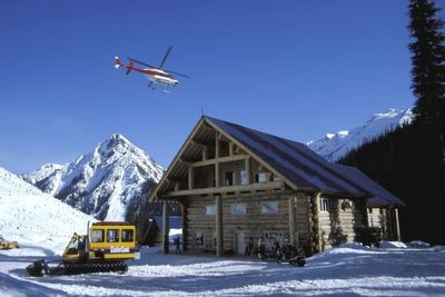 Dan Hudson photographs Chatter Creek's Vertebrae Lodge with departing helicopter and waiting snowcat