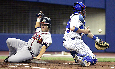 Marcus Giles slides safely into home past Expos Catcher Brian Schneider