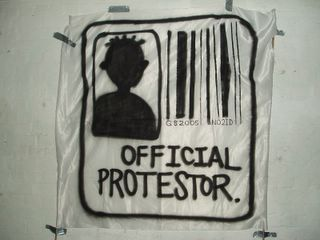 Photo of a spray painted Official Protester sign, containing a bar code under which is written G82005 NO2ID