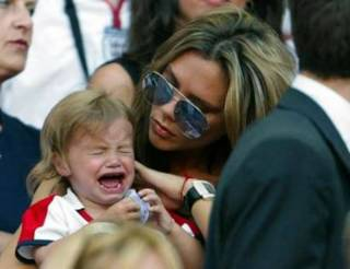 Victoria Beckham comforts her son Romeo during England's Group B Euro 2004 soccer match against France at the Luz Stadium in Lisbon June 13, 2004. David Beckham missed a penalty in England's 2-1 loss to France. REUTERS/Darren Staples