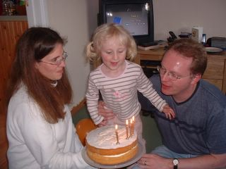 Daddy blowing out his candles, with a bit of help from Hannah