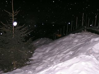 Snowy stairs descending into a freezing lake somewhere in the darkness