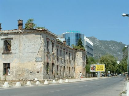 An empty, bombed buliding in Mostar and a newly-built glass-and-steel building close to each other