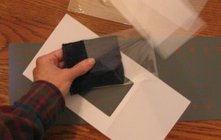 Placing a handwoven fabric sample in a plastic sleeve.