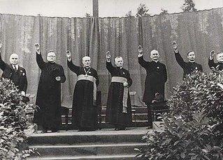 Sacerdotes católicos españoles alzando el brazo para efectuar el saludo fascista durante la dictadura criminal y genocida de Franco