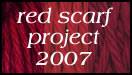 red scarf project 2007 button featuring white letters over strands of red yarn