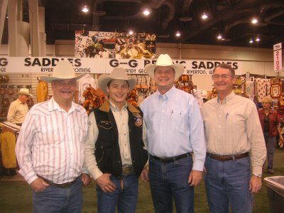 Photo of Roland Lee with cowboy Cody Wright, Lyman Hafen, and kelton Hafen at the National Finals Rodeo in 2006