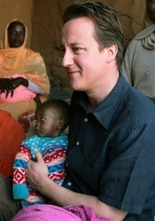 Cameron cuddles African child, the great big poof
