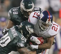 The Giants' Tiki Barber can't shake off the Eagles' Brian Dawkins and Mike Patterson. (AP)