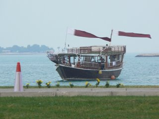 A dhow passes by, with national flags fluttering proudly