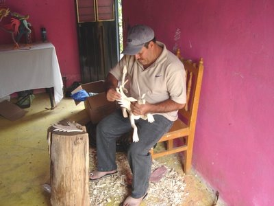 Pale Horse Galleries online store for gifts, collectibles, Mexican art and crafts. http://palehorsemex.vstore.ca/ Fidencio Ojeda, Zapotec sculptor of wooden figures and alebrijes, at work with a new creation in Arrazola, Xoxocotlan, Mexico.