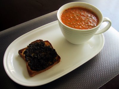 Large cup of tomato soup and toast on a plate. Underneath is a plastic placement.