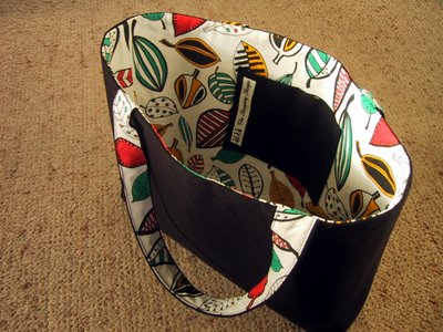 Black shopping tote with a lining made of colourful fabric printed in a leaf design.