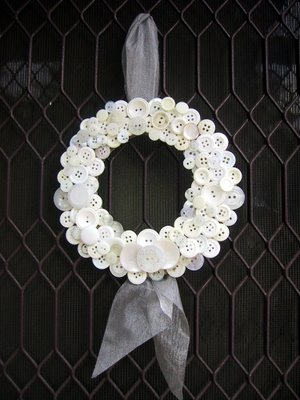 A white button wreath hanging on a screen door.