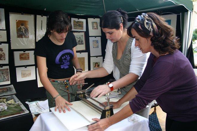 Candela Sanchez, Esther Melguizo, y Maximina Espeso, ajustando la presión del torculo.