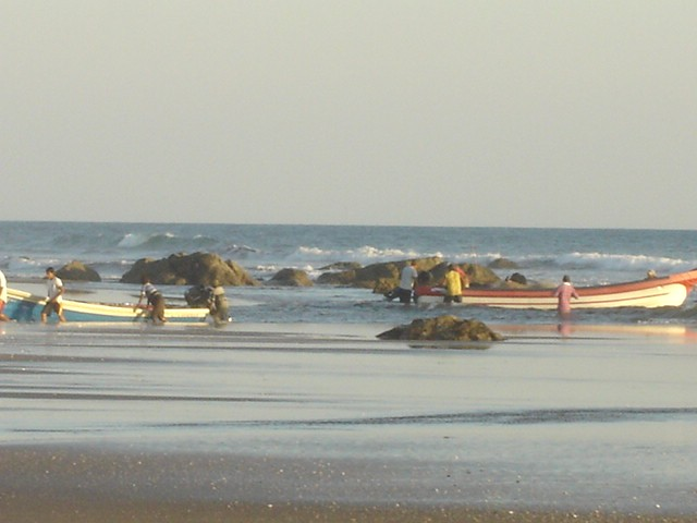 Las Peñitas fisherman pushing boats in & out during low tide