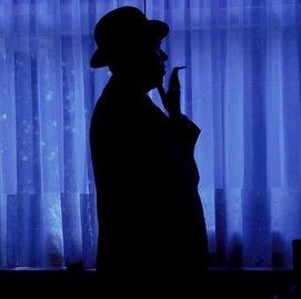 Sombrero en la sombra fumando girado a la derecha. Fondo azulado decorando un montaje fotográfico