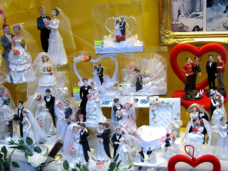 This is a photo of the shop display of a downtown decoration store. Since it's the wedding season, they have all kinds of wedding couples to put on the big ...