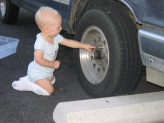 Matthew on his knees reaching out his arm and touching a car tire.