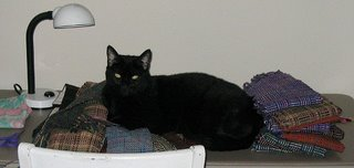 Rascal, making himself at home on my neat pile of handwoven log cabin scarves.