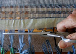 Cutting the knots off the warp.  This took nerve!