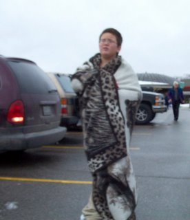 Kid in parking lot wrapped in blanket