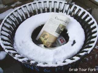 Snow-encrusted garbage bin with yesterday's newspaper