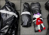 Three of some 300 'body bags' laid out in Sydney's business district in remembrance of civilians killed in recent conflicts across the world