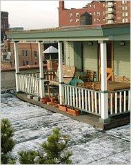 Casa con porche y jardín en lo alto de un edificio