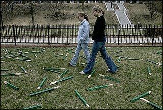 College of The Holy Cross students Sarah Fontaine (left) and Molly Haglund, who helped create the installation on the Iraq war, passed through the vandalized display yesterday. (Suzanne Kreiter/ Boston Globe Staff photo)