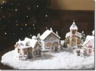 As A Soft Decorative Fake Snow Falls On The Christmas Village