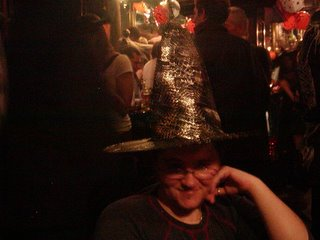 Me wearing a witches hat with silver cobwebs on it