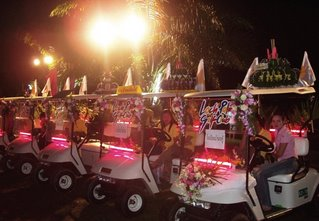 Golf carts from the country club carry kratongs