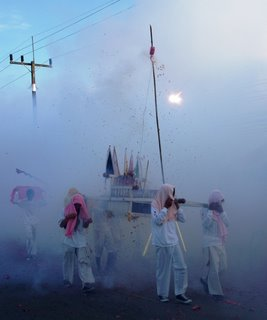 Carrying the god statues through the smoke and firecrackers