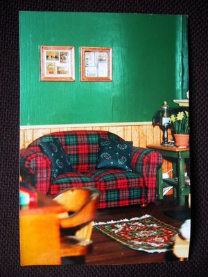 Dolls' house miniature study, with green painted walls with wainscoating, and a green and red plaid sofa.