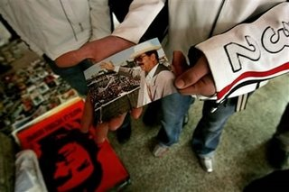 "Picture: a ""Palestinian"" holds a photo of Saddam in mourning, while on the floor is the black-and-red Ché imprint"