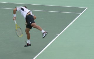 The Japanese tennis player leaves the ground as he puts all his effort into his serve