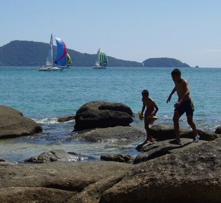 A couple of local lads run across the rocks as the boats sail past Laem Ka Beach
